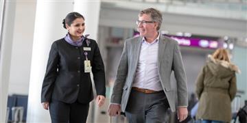Greeter walking with passenger through the airport terminal.