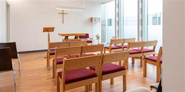 Rows of cushioned wooden benches in prayer room.